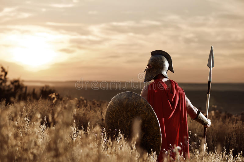 Warrior wearing iron helmet and red cloak. Back view of warrior man wearing iron helmet and red cloak holding sword, soldier looking and turned back. Male royalty free stock photography
