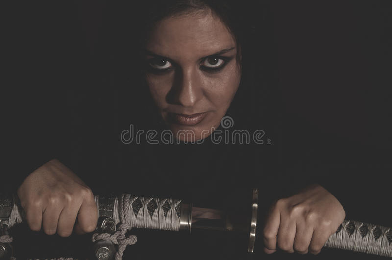 Warrior wild woman with black hair and iron sword. Dangerous royalty free stock photos