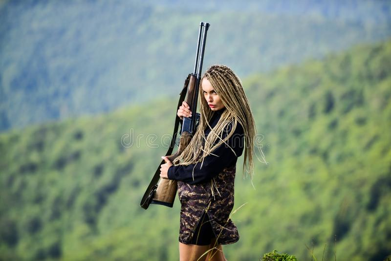 She is warrior. Woman attractive long hair pretty face hold rifle for hunting. Dangerous girl. Defending concept royalty free stock image