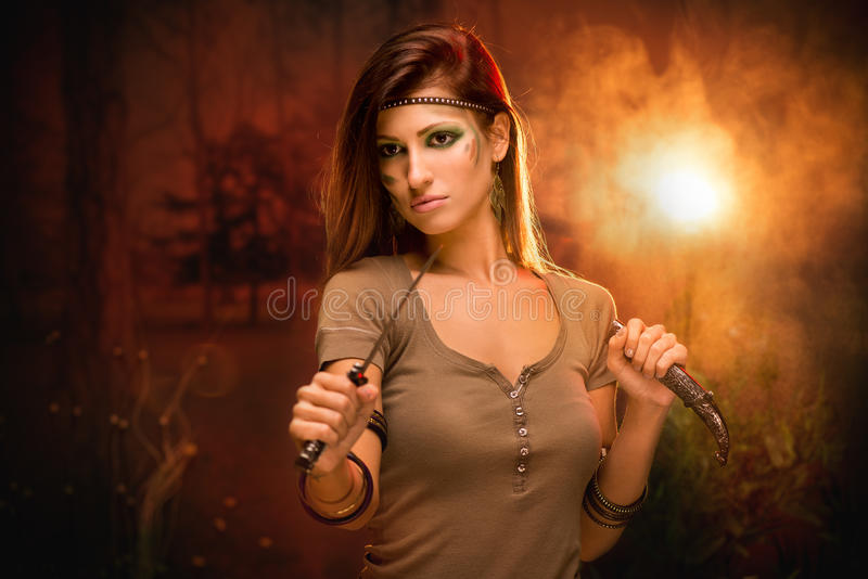 Warrior Woman With Combat Knife. Portrait of a warrior woman with combat knife at sunset stock photography