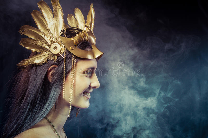 Warrior woman with gold mask, long hair brunette. Long hair. Pro. Valkyrie, Golden statue concept. Arty portrait of model with golden mask and shiny lashes stock photography