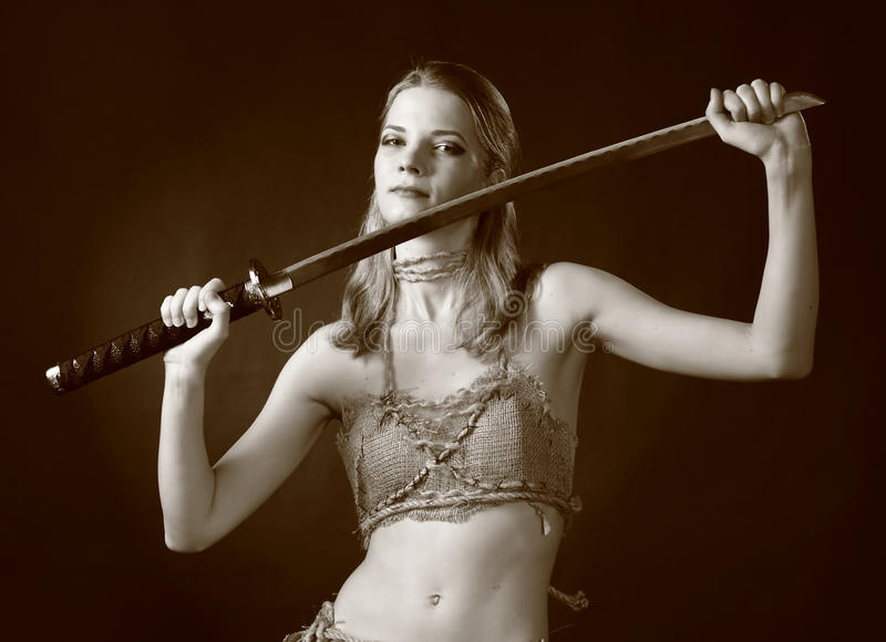 Warrior woman with sword. Studio shot of Antique clothing young warrior woman holding sword in her hand royalty free stock image