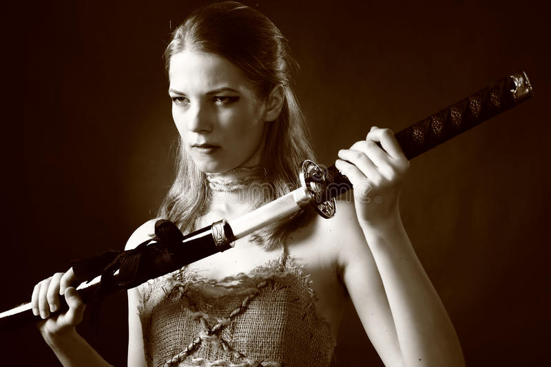 Warrior woman with sword. Studio shot of Antique clothing young warrior woman holding sword in her hand royalty free stock photography