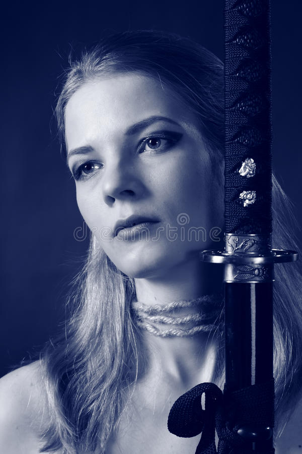 Warrior woman with sword. Studio shot of Antique clothing young warrior woman holding sword in her hand royalty free stock images