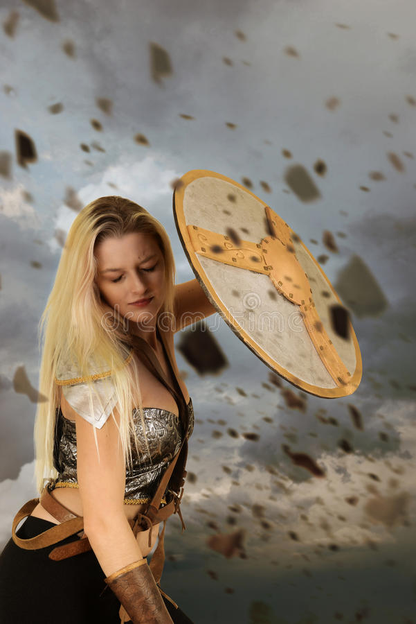 Warrior woman using shield to block flying rocks. Portrait of warrior woman using shield to block flying rocks stock photography