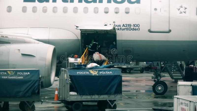 WARSAW, POLAND - DECEMBER 25, 2017. Loading mail onto the Lufthansa airplane at the Chopin international airport stock photo