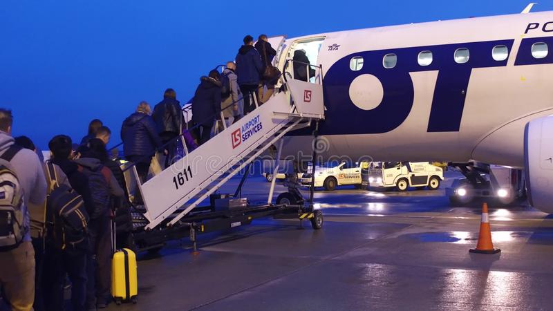 WARSAW, POLAND - DECEMBER, 23 People boarding LOT airlines plane on the airfield royalty free stock photography