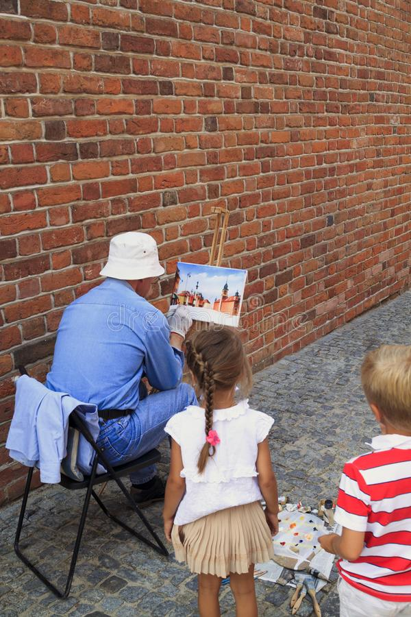WARSAW, POLAND - June 29, 2018 - boy with girl watching as a street artist draws a vintage house stock photo
