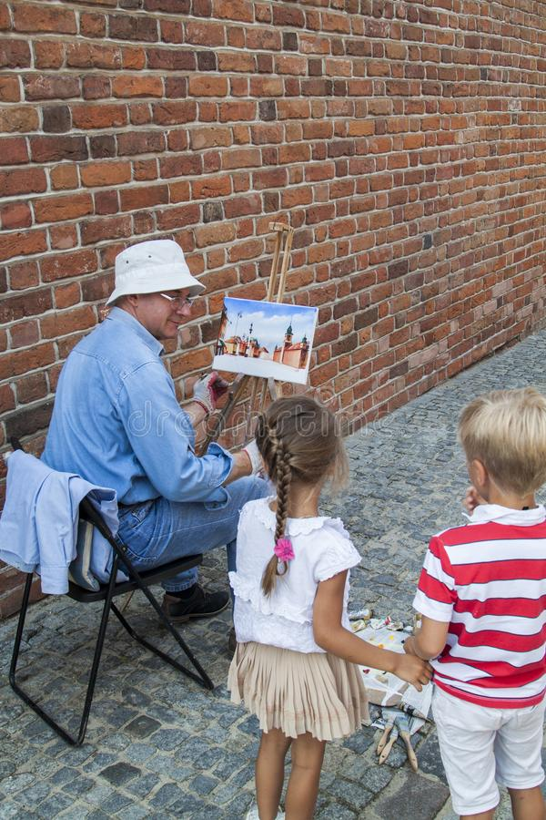 WARSAW, POLAND - June 29, 2018 - boy with a girl watching as a street artist draws a vintage house stock photos
