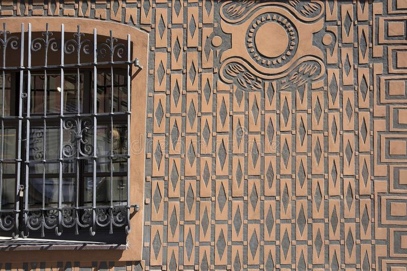 Figured plaster texture, bars in the square window and iron door. royalty free stock photography