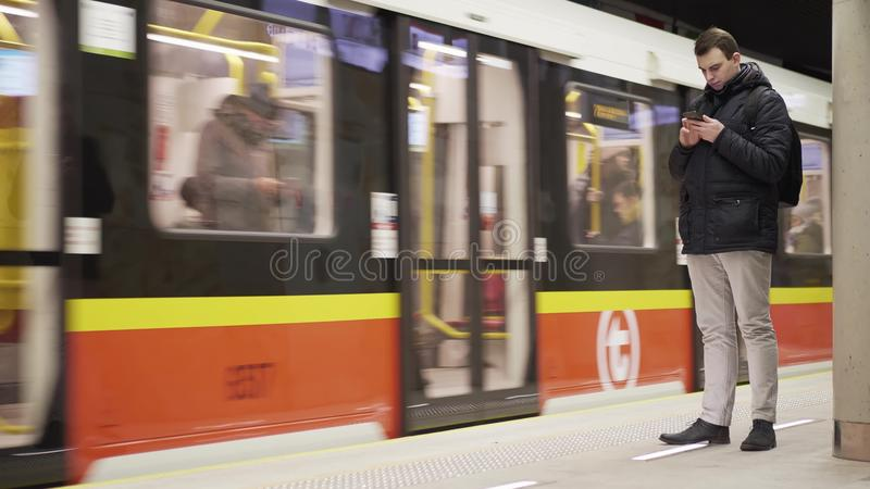 WARSAW, POLAND - MARCH 1, 2018. Young man with smartphone and subway train arriving to Rondo ONZ metro station royalty free stock image