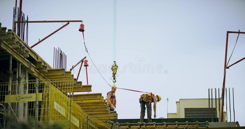 WARSAW, POLAND - MAY 24, 2019. Two workers on a residential building construction site. WARSAW, POLAND - MAY 24 2019 Two construction workers royalty free stock images