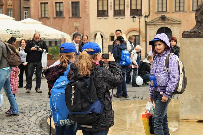WARSAW, POLAND - MAY 12, 2012: Unknown tourists take pictures in the Warsaw Old Town Market Place stock image