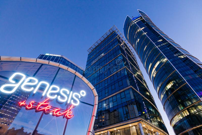 Warsaw Spire Office Building. Warsaw, Poland - Oct 21, 2018: Office building Warsaw Spire at Night and the neon sign of a popular steak restaurant called Genesis stock images