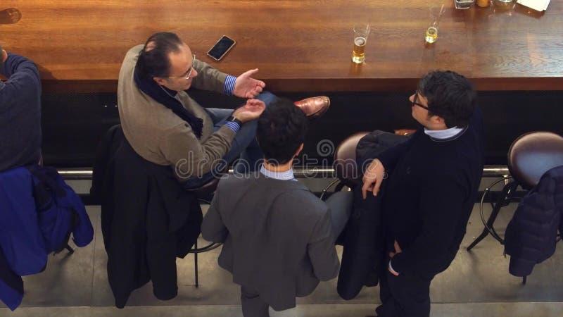 WARSCHAU, POLEN - DEZEMBER, 22, 2016 Mittel-gealterte Geschäftsmänner, die Gespräch an der Stange, Draufsichtschuß haben lizenzfreies stockfoto