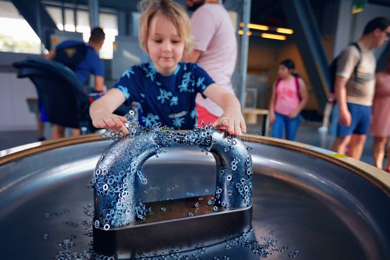 WARSCHAU, POLEN - 20. Juni 2019: Kind, welches die Eigenschaft von Magneten und von seinem effection auf den Metallen erforscht D lizenzfreies stockfoto