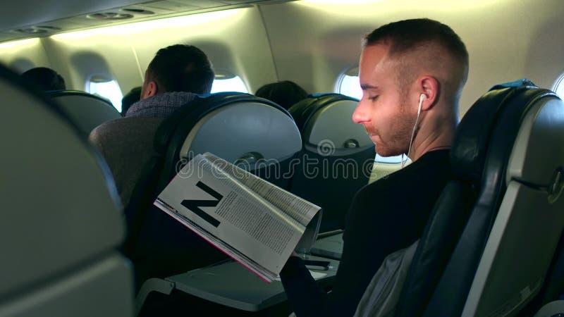 WARSHAU, POLEN - DECEMBER, 24, 2016 Jonge mens die aan de muziek luisteren en tijdschrift in vliegtuigcabine lezen stock foto