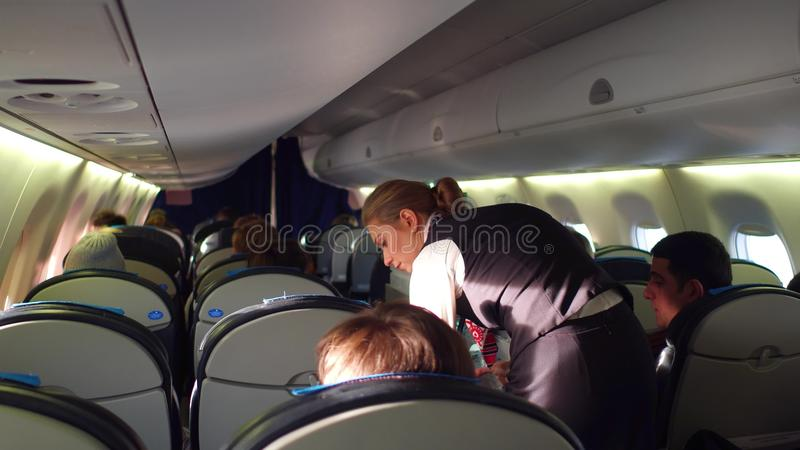 WARSHAU, POLEN - DECEMBER, 24 PARTIJ Vrouwelijke steward bij het werk en lijnvliegtuigpassagiers in de cabine stock afbeelding