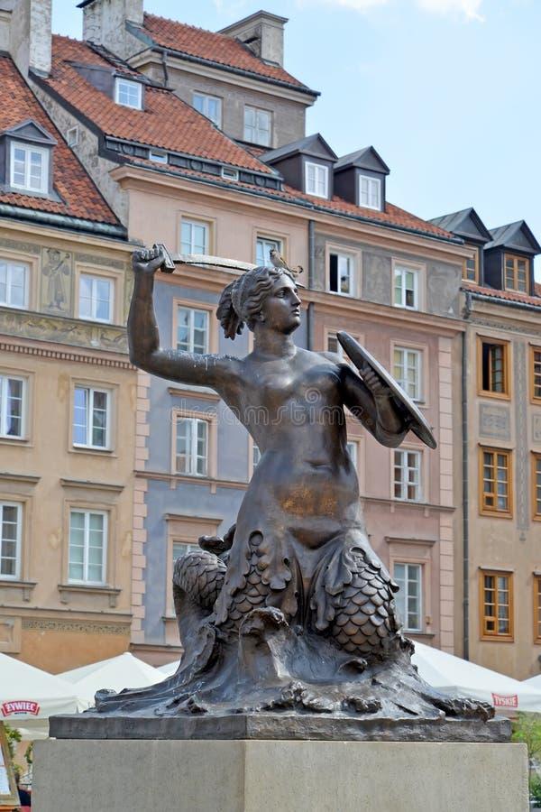 Warshau, Polen Een standbeeld van de sirene van Warshau tegen de achtergrond van historische gebouwen stock afbeelding