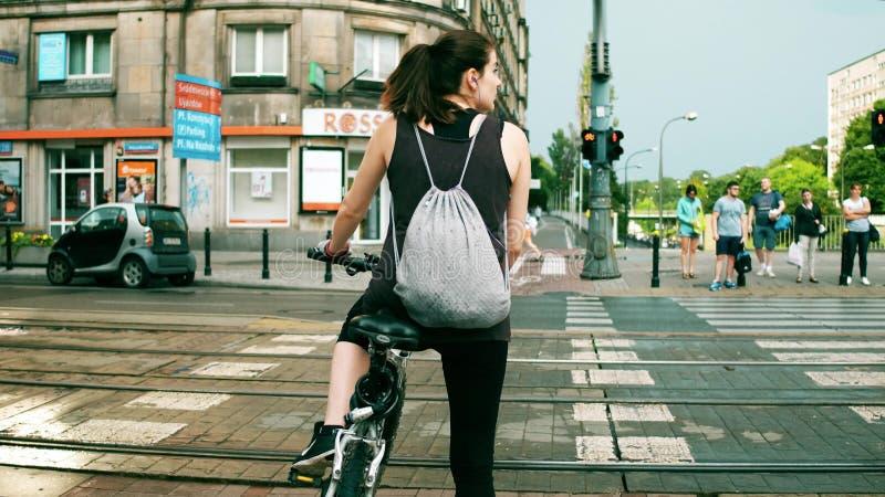 WARSHAU, POLEN - JULI 11, 2017 Jonge atletische vrouwelijke fietser die bij het zebrapad van de stadsstraat wachten stock afbeeldingen