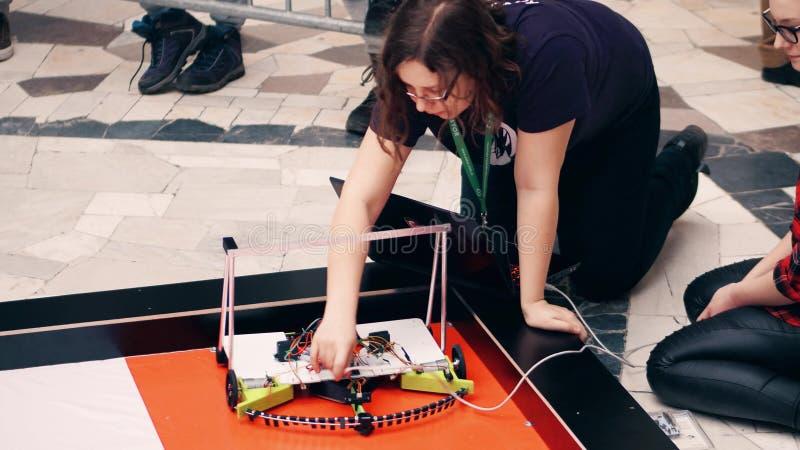 WARSHAU, POLEN - MAART, 4, 2017 DIY-robot en jonge vrouwelijke deelnemer van de roboticaconcurrentie stock foto