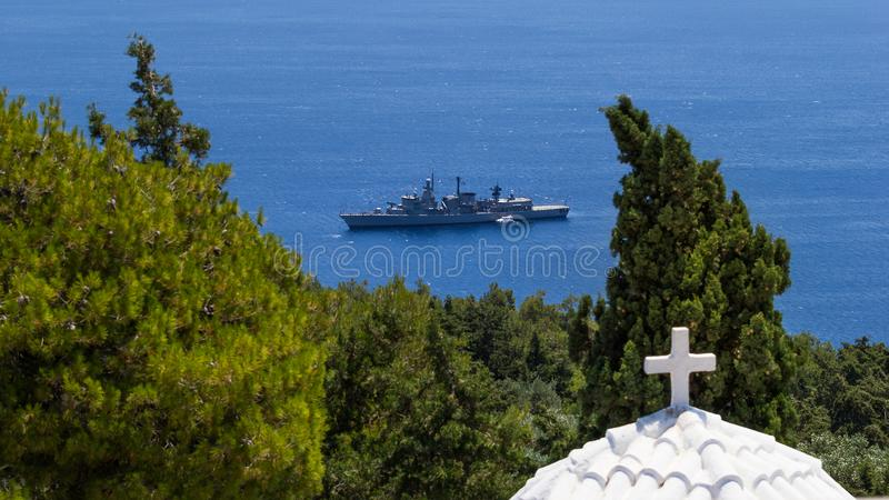 Religion and war. Warship moored in the bay on the tele-cross royalty free stock photos