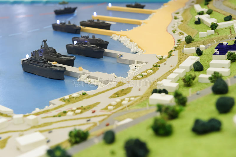 Warships wharf scale model. Layout of army naval base, miniature of military harbor with small models of ships, piers, docks, buildings and port driveways stock photography