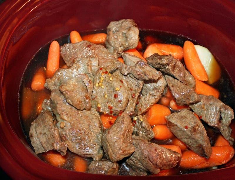 Warstwy grule, marchewki i brązowić stewing wołowina w wolnej kuchence z pikantność i dodającym wołowina rosołem przygotowywający obraz royalty free