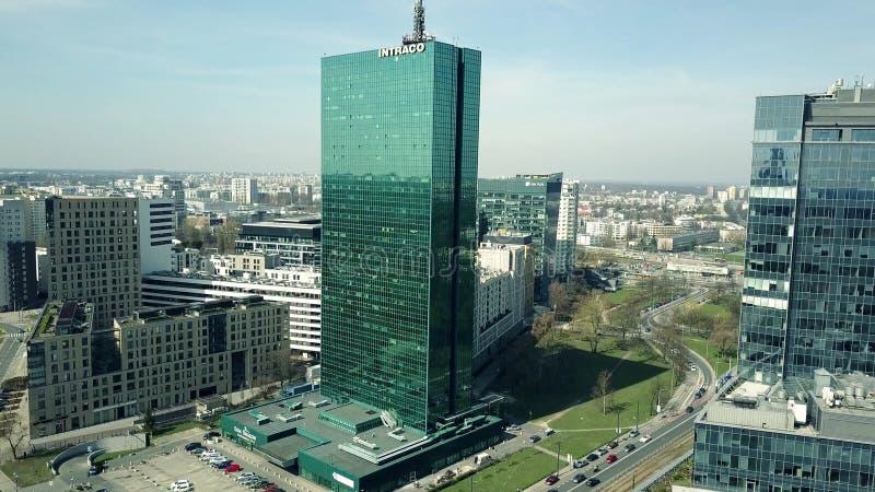 WARSZAWA POLEN - APRIL, 1, 2017 Antennskott av modern kontorsbyggnad med reflekterande cityscape för INTRACO-överskrift på a royaltyfri fotografi