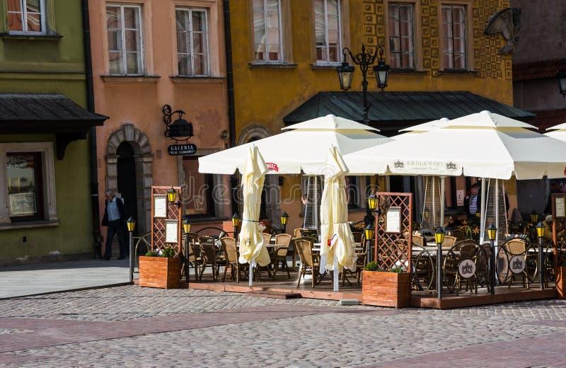 WARSZAWA POLEN - APRIL 21, 2016: Gatakafé på solig dag i gammal stad i Warszawa, Polen royaltyfri bild