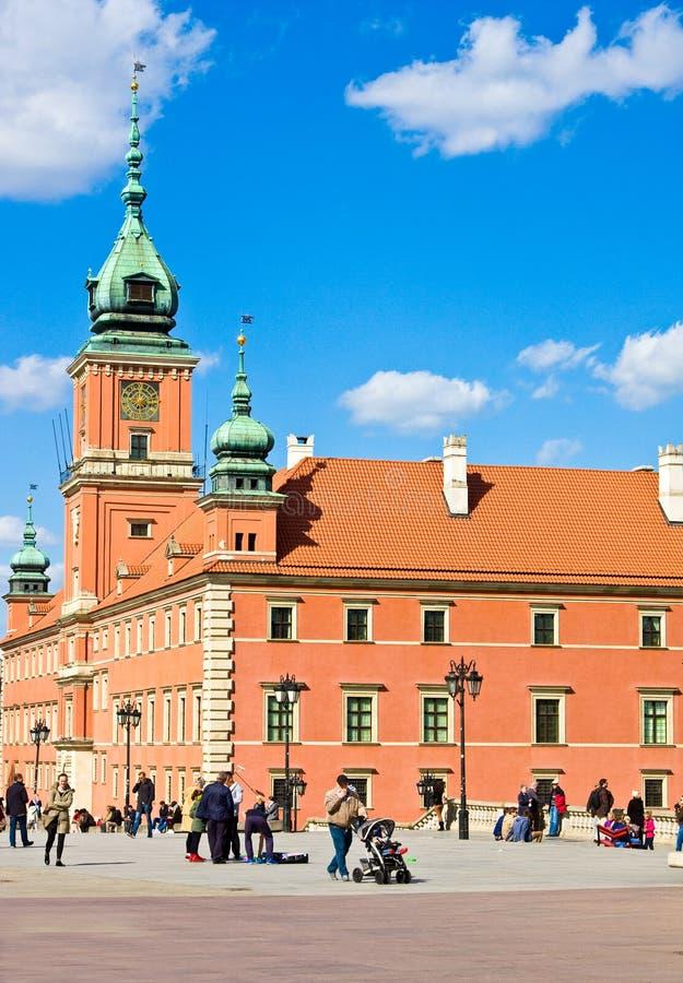 WARSZAWA POLEN - APRIL 21, 2016: Turister går nära konungslott i gammal stad av Warszawa arkivfoto