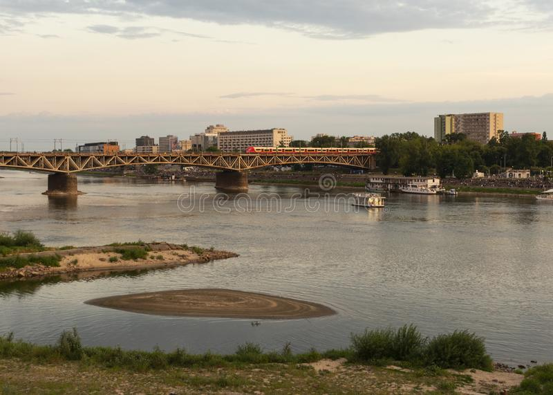 Warszawa, Polen/Europa. 12/07/2019: Järnvägsbron över floden Vistula vid solnedgången i Warszawa, Polen royaltyfri foto