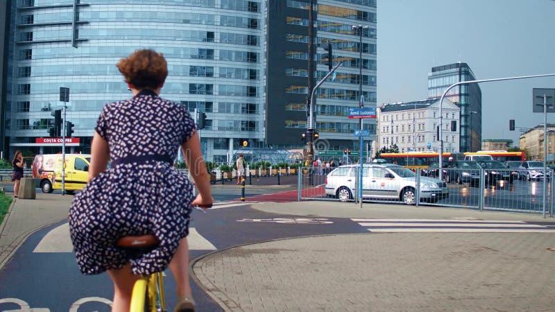 WARSZAWA POLEN - JULI 11, 2017 Ung kvinna som rider hennes klassiska cykel i staden arkivbild