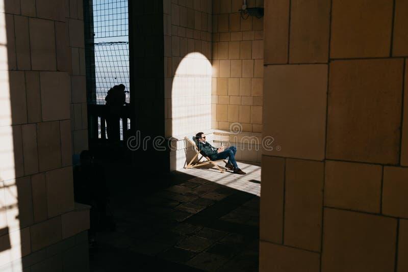 WARSZAWA POLEN, OKTOBER 14 2018 - man som kopplar av på synvinkelterrassen av slotten av kultur och vetenskap royaltyfri fotografi