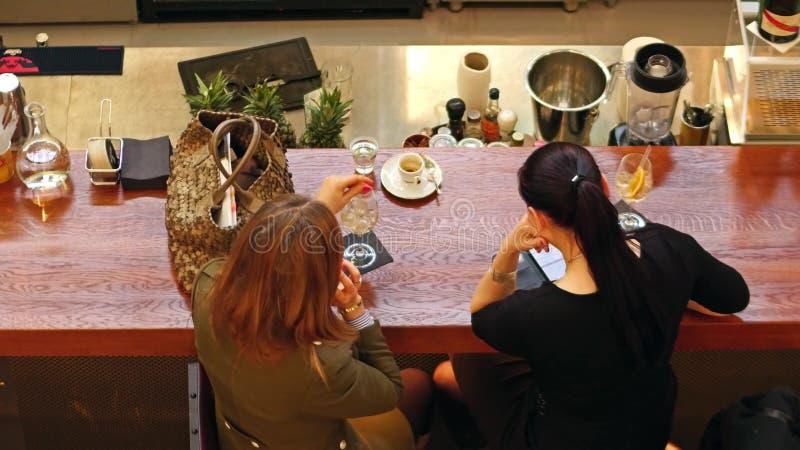 WARSZAWA POLSKA, MARZEC, -, 4, 2017 Żeńscy przyjaciele używa smartphone i mieć napój przy barem obrazy stock