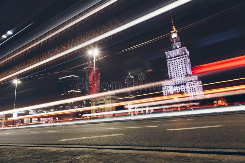 Warszawaljusslingor på stadsgatan på natten - BILLJUS SKUGGAR Polen royaltyfri bild