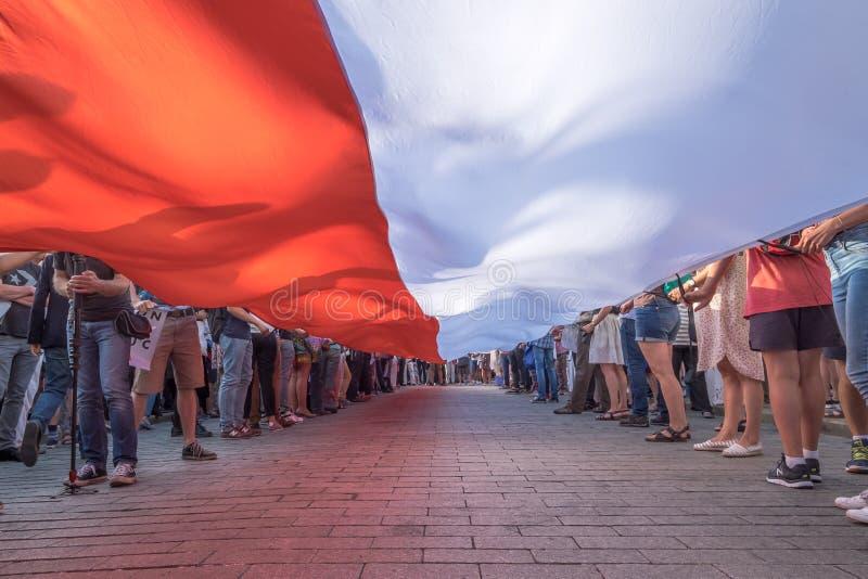 Warszawski Polska, Lipiec - 24, 2017: Tysiące protestujący niosą giganta połysku flagę zdjęcie royalty free