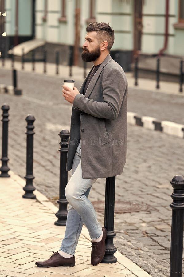 Warten auf jemand in der Stra?e Hippie-Getr?nkkaffee-Papierschale des Mannes b?rtige Der gepflegte Gesch?ftsmannbrunnen genie?en  lizenzfreies stockfoto