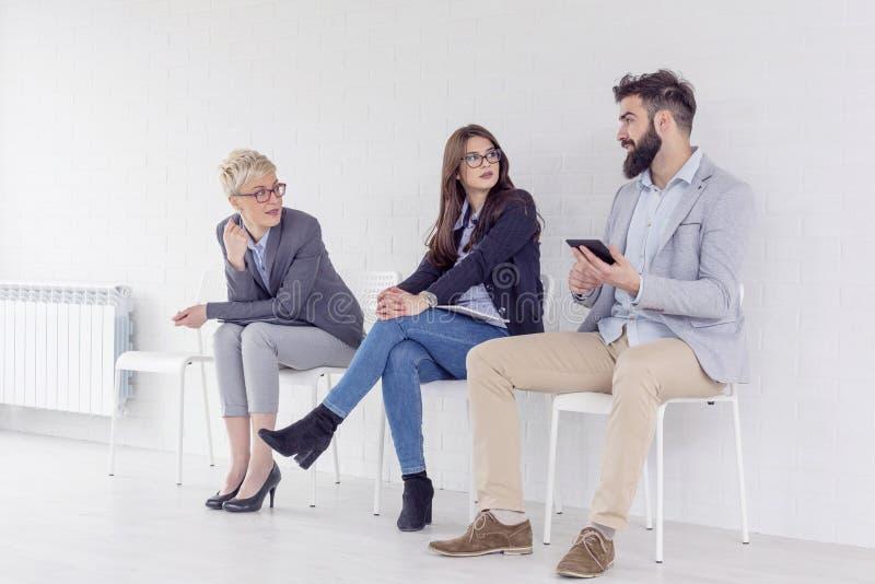 Wartende und sitzende Gruppe von Personen stockfoto