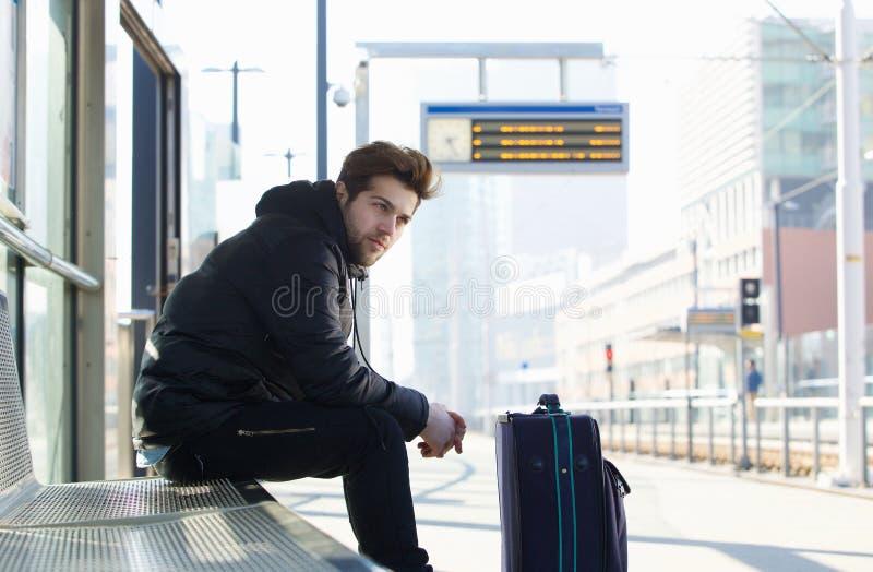 Wartezug des jungen Mannes mit Kofferreisetasche stockbild