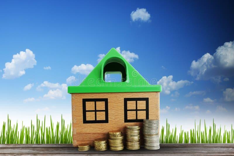 Wartości nieruchomości wzrostowy pojęcie z drewnianym domem i skala pieniądze przeciw naturalnemu tłu zdjęcia stock