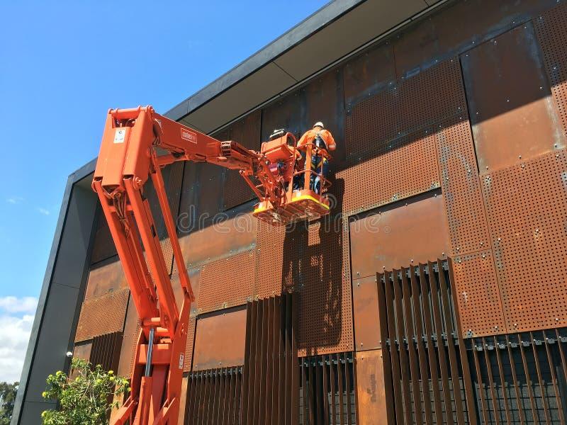 Wartungsarbeiter auf orange Cherry Picker Crane lizenzfreies stockfoto
