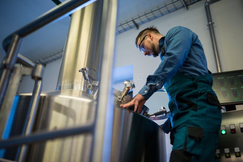 Wartungsarbeiter, der an der Brauerei arbeitet lizenzfreies stockbild