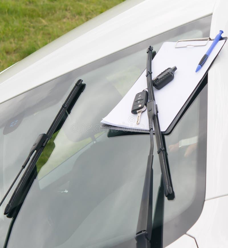 Wartungsdokumente und Autoschlüssel, auf der Windschutzscheibe des Autos lizenzfreies stockfoto