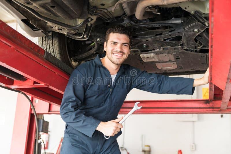 Wartungstechniker Holding Wrench While, das unter Auto steht lizenzfreie stockfotos