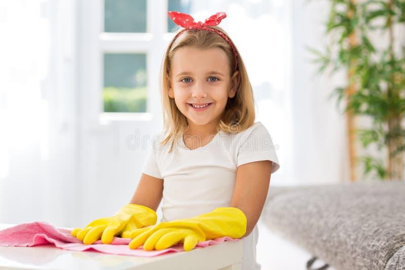Warty uśmiechniętą młodą dziewczynę z rękawiczkami czyści do domu obraz stock