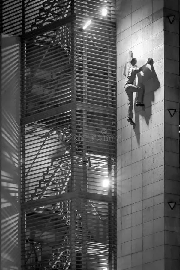 Warum man nicht die Treppe nimmt? Mann-kletterndes errichtendes Äußeres stockfoto