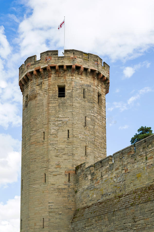 Warwick castle tower. Close up of the Warwick castle tower with a flag of England stock photography