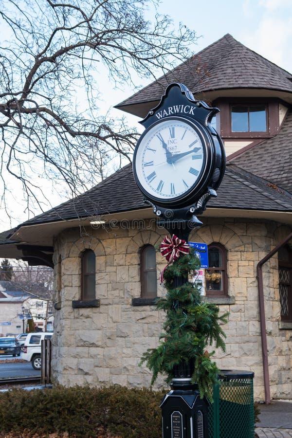 Warwick, NY Vereinigte Staaten - 4. Januar 2019: Warwicks Eisenbahn-Grün-Postenuhr und -station lizenzfreies stockbild