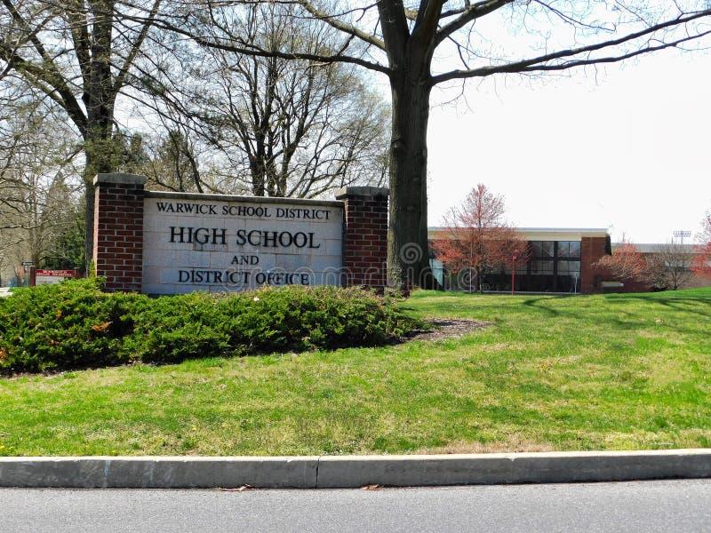 Warwick skoldistrikt- och högstadiumtecken med hög skola i bakgrund arkivfoto